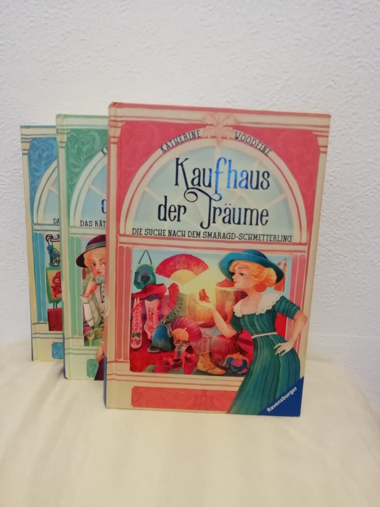 """Cover von """"Kaufhaus der Träume"""" Band 2, Schaufenster im Hintergrund, blonde Dame mit einem Schmetterling in der Hand im Vordergrund;"""